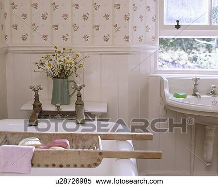 Old wooden bath rack on white rolltop bath with reclaimed taps in cottage  bathroom with panelling and floral wallpaper. Stock Image of Old wooden bath rack on white rolltop bath with