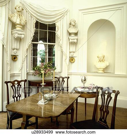 Stock photograph of classical busts on wall plinths and in for Neoclassical dining room design