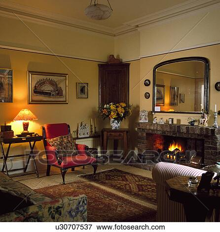 image grand miroir au dessus chemin e clair br ler dans jaune salle de s jour. Black Bedroom Furniture Sets. Home Design Ideas