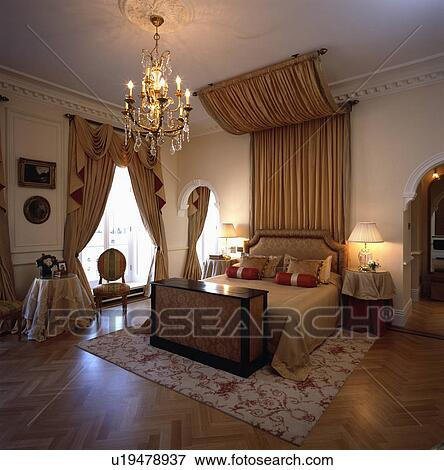 Canopy with coffee silk drapes above bed in opulent bedroom with lighted chandelier and parquet floor & Picture of Canopy with coffee silk drapes above bed in opulent ...