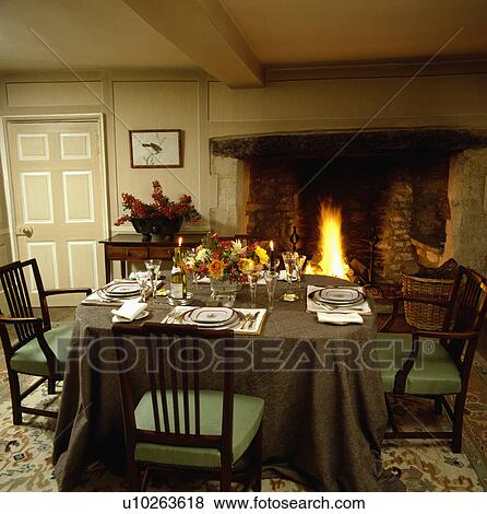 Place Settings And Floral Arrangement On Table With Brown Cloth In Front Of Fireplace Country Dining Room