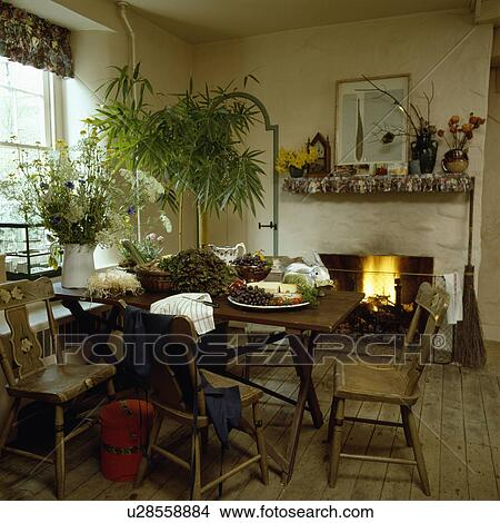 Small Country Dining Room With Lighted Fire In Fireplace And Old Wooden Table Chairs On Flooring