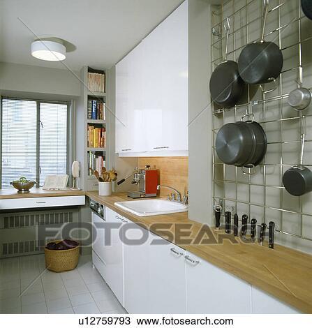 Stock foto pannen op metaal wall mounted opslagrek in hippe witte kombuis keuken met - Kombuis keuken ...