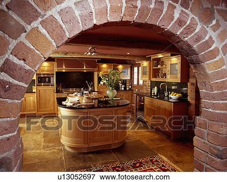 Immagine vista attraverso mattone arco di tradizionale legno cucina con ovale isola - Cucina con arco ...