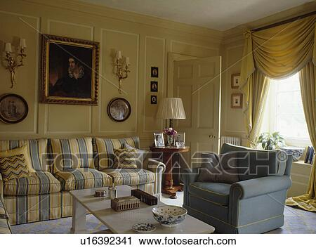 Stock Photography   Yellow And Blue Striped Sofa And Blue Armchair In Cream  Panelled Living Room Part 93