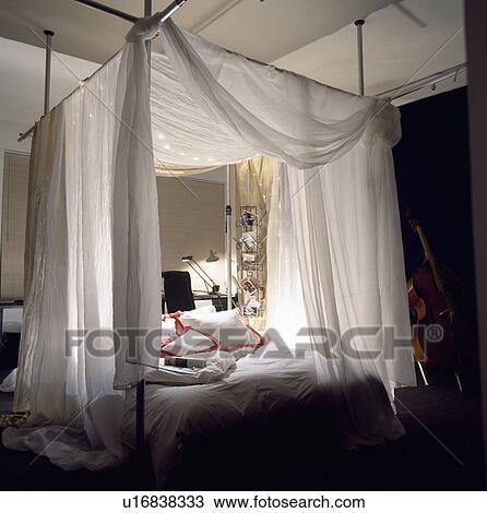 banque de photo blanc voile tentures sur moderne m tal lit baldaquin dans moderne. Black Bedroom Furniture Sets. Home Design Ideas