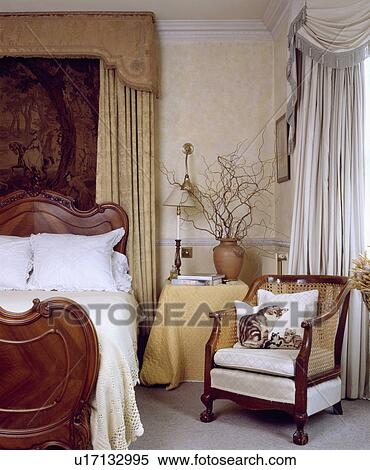 Stock Image of Silk drapes above mahogany bed in neutral bedroom ...