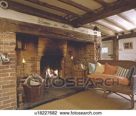 Baskets Of Logs In Inglenook Fireplace Beamed Cottage Living Room With Wicker Sofa And Sisal Carpet