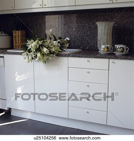 stock images of white lilies in sink in modern white kitchen with