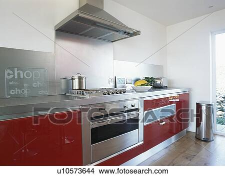 Stock photo of steel extractor above range oven in large for Red fitted kitchen