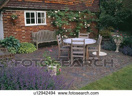 Stock Photo   Wooden Table And Chairs On Herringbone Brick Paved Patio In  Front Of