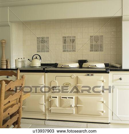 stock photo of cream wall tiles above cream double aga. Black Bedroom Furniture Sets. Home Design Ideas