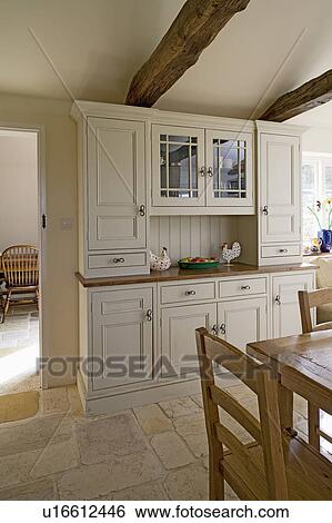 Cream Painted Dresser In Traditional Country Kitchen Dining Room With Antique Jerusalem Stone Flooring