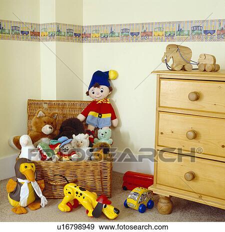 Stock fotografie mandje van kleurrijke zachte speelgoed naast dennenboom ladenkast in - Pastel slaapkamer kind ...