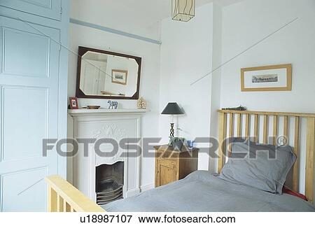 Picture of mirror above fireplace in small white bedroom for Small mirrors above bed