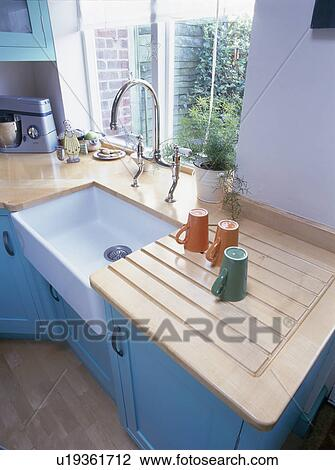 Cups On Draining Board Beside White Ceramic Sink In Turquoise Kitchen