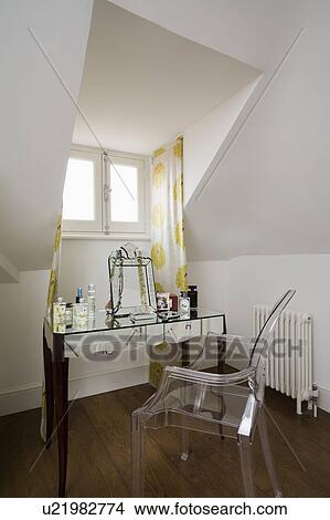 Philippe Starck perspex Ghost chair at mirrored dressing table in attic  bedroom