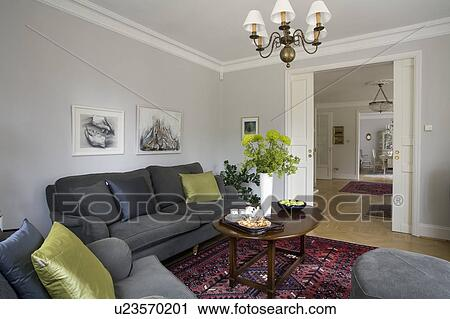Stock photography of lime green cushions on charcoal grey sofas in pale grey living room with for Charcoal and red living room