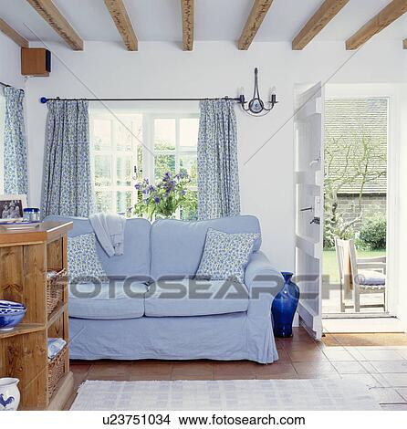 banque de photo bleu loosecover sur sofa devant fen tre dans blanc petite maison. Black Bedroom Furniture Sets. Home Design Ideas