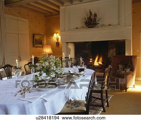 Antique China And White Linen Cloth On Long Table In French Country Dining Room With Large Stone Fireplace