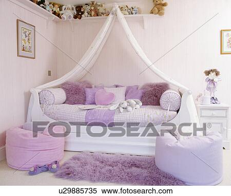 stock bild wei vorh nge oben bett mit mauve leinen und kissen in rosa jugendlich. Black Bedroom Furniture Sets. Home Design Ideas