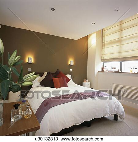 Stock Photo of Wall-lights on brown wall above bed with white duvet in modern bedroom with cream ...