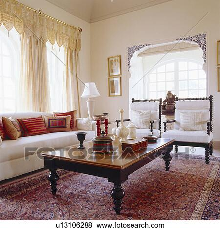 Embroidered Cushions On Cream Sofa In Rajastani Livingroom With Wooden  Table And Carvet Armchairs On Indian Carpet