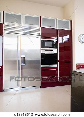 Large Stainless Steel American Style Fridge Freezer In Modern Kitchen With  Double Oven In Black Fitted Unit