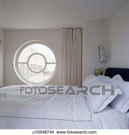 banque de photo circulaire fen tre c t de lit blanc lin dans moderne blanc. Black Bedroom Furniture Sets. Home Design Ideas