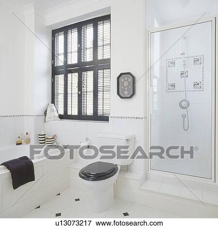 white toilet with black seat. Black plantation shutters above bath and black toilet seat in modern white  bathroom with glass shower door Picture of