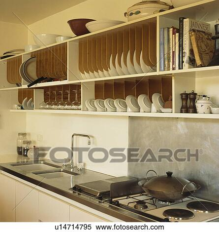Modern Kitchen Racks stock image of fitted wooden plate racks above sink in modern