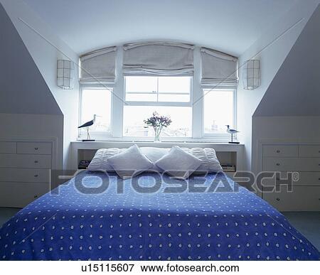 immagine blu bedlinen letto sotto finestra in