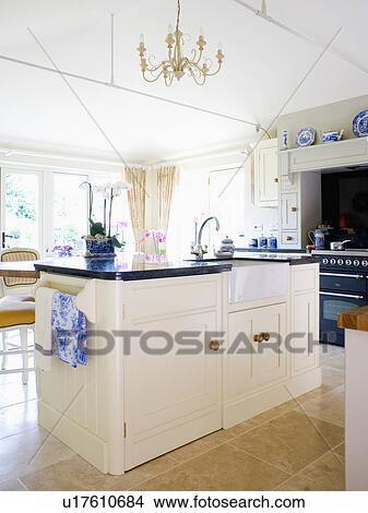 stock photo of sink in cream island unit with black granite