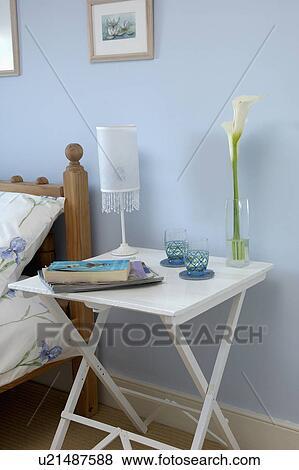 Beelden lamp en boekjes op klein witte geverfde nachtkastje in pastel blauwe - Pastel slaapkamer kind ...