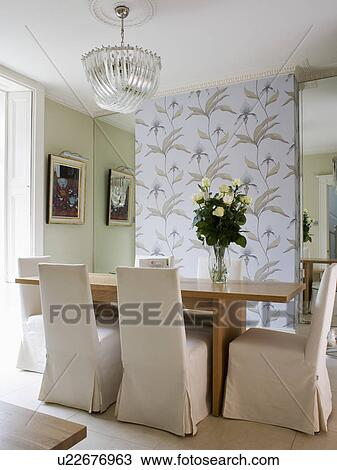 Beige Loose Covers On Chairs At Wooden Table In Modern Pale Green Dining Room With Panel Of Wallpaper