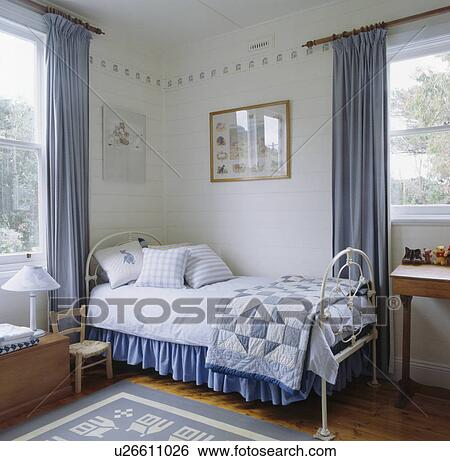 Blue patchwork quilt and white linen on white bed in blue white themed  bedroom. Stock Images of Blue patchwork quilt and white linen on white bed