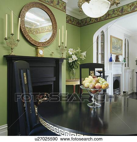 banques de photographies ovale miroir au dessus noir chemin e dans vert salle manger. Black Bedroom Furniture Sets. Home Design Ideas