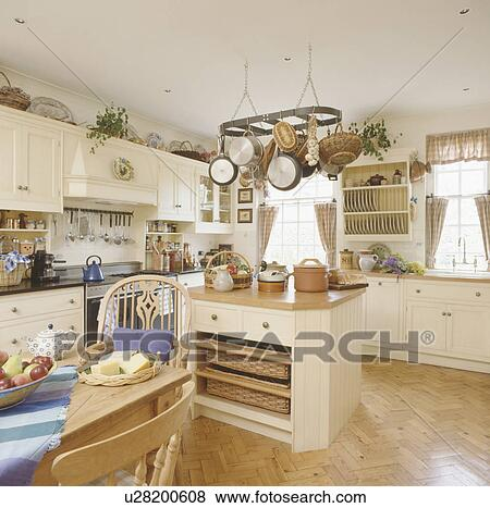 pictures of pans on rack above island unit with storage baskets on