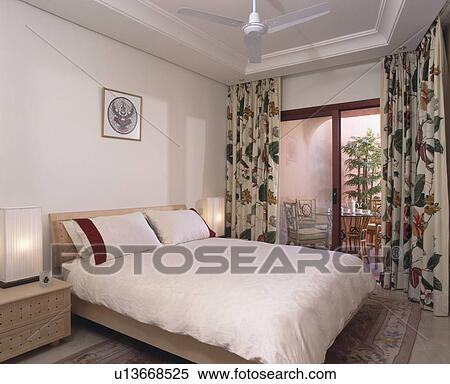 Floral Curtains On Patio Doors To Balcony In Modern Spanish Apartment  Bedroom