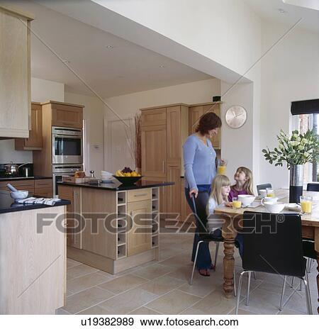 banque de photographies m re et deux petit filles table dans moderne cuisine u19382989. Black Bedroom Furniture Sets. Home Design Ideas