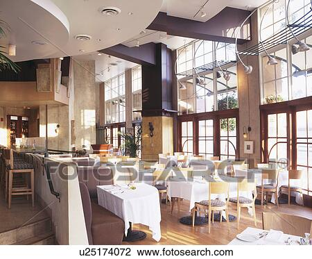 Stock Photo   White Cloths On Table With Pale Wood Chairs In Modern Double  Storey Restaurant