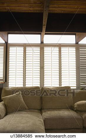 Stock Image   Plantation Shutters Over Sofa. Fotosearch   Search Stock  Photos, Mural Pictures