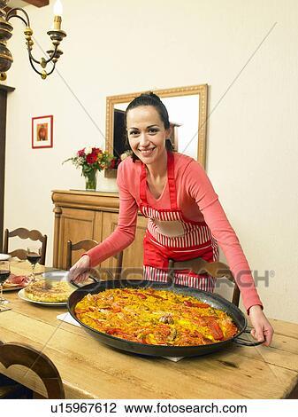 banque de photo jeune femme mettre grand plat de paella sur table haute sourire. Black Bedroom Furniture Sets. Home Design Ideas
