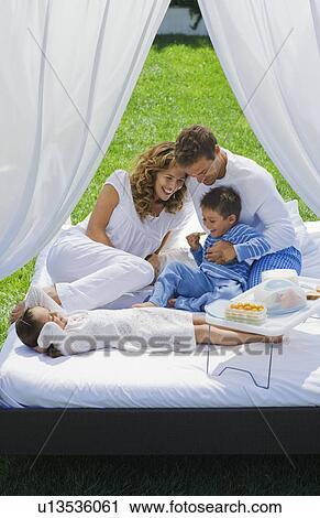 stock fotografie familie haben fruehstueck bett in kleingarten u13536061 suche. Black Bedroom Furniture Sets. Home Design Ideas