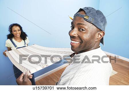 Stock fotografie paar het uitrollen zich behang in kamer achtermening u15739701 zoek - Behang volwassene kamer behang ...