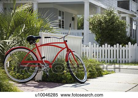 Stock Image Of Red Beach Cruiser Bicycle Propped Against Fence In Front Of Ho