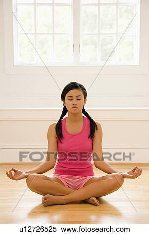 Stock image of woman sitting on floor meditating in yoga for Pose poster mural
