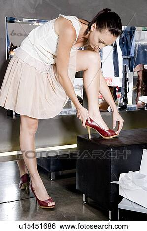 Stock Image - Woman trying on high-heeled shoes in a shoe shop. Fotosearch