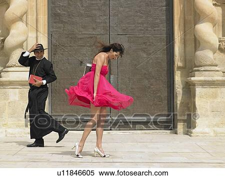 Priest passing woman whose skirt is blowing up in the wind alicante
