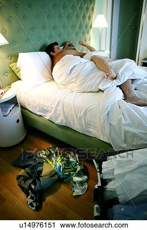 stock photography of couple under the covers in bed with